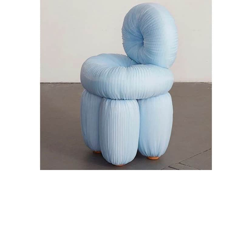 Sculptural piece of art of upholstered and puffy baby blue small armchair with backrest